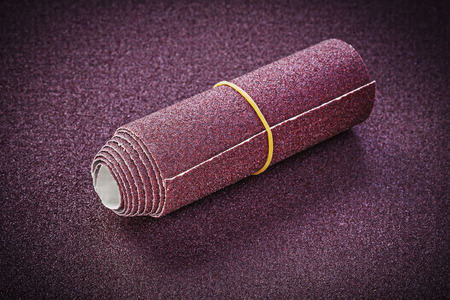 emery paper: Rolled up glass-paper on polishing sheet abrasive materials. Stock Photo