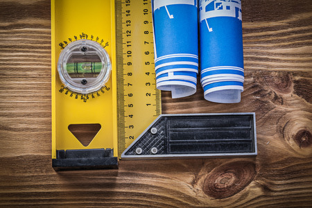 square ruler: Blue engineering drawings construction level square ruler on wooden board.