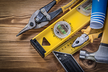 square ruler: Blue blueprints construction level square ruler claw hammer pliers steel cutter on wooden board. Stock Photo