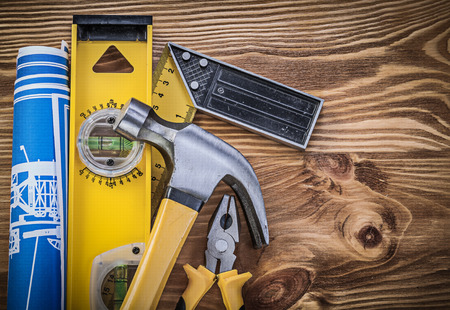 square ruler: Blue blueprints construction level square ruler claw hammer gripping tongs on wooden board.