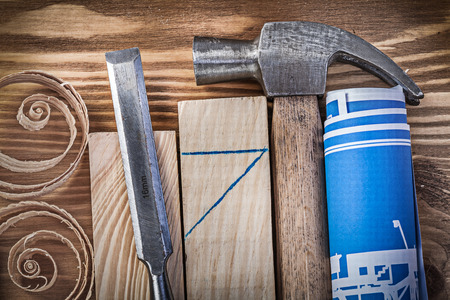scobs: Blue rolled construction drawing claw hammer firmer chisel wooden studs curled shavings on vintage wood board. Stock Photo