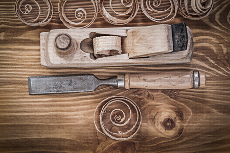 curled: Planer chisels curled shavings on vintage wooden board construction concept. Stock Photo