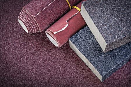 emery paper: Glass-paper rolls sanding sponges on polishing sheet abrasive materials. Stock Photo