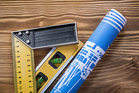 square ruler: Blue construction drawing level square ruler on wooden board. Stock Photo