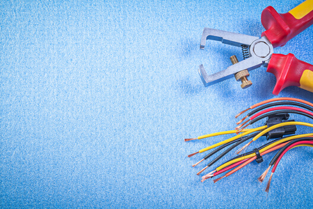 electricity background: Insulated wire strippers electrical cables on blue background copy space electricity concept. Stock Photo