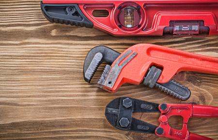 pipe wrench: Bolt cutter construction level pipe wrench on vintage wooden board maintenance concept. Stock Photo
