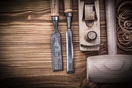 wood planer: Lump hammer planer firmer chisels planning chips on vintage wood board construction concept.