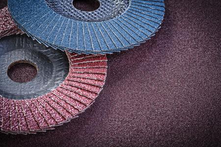 emery paper: Abrasive flap wheels on sandpaper sheet top view.