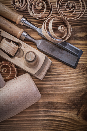 scobs: Firmer chisels shaving plane curled shavings wooden mallet on wood board construction concept.