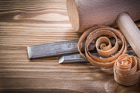 scobs: Lump hammer firmer chisels curled shavings on vintage wood board construction concept.