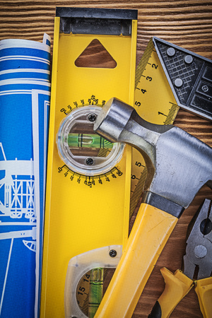 square ruler: Blue engineering drawings construction level square ruler claw hammer gripping tongs on wooden board.
