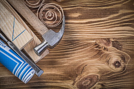 scobs: Blue construction plan claw hammer flat chisel wooden studs shavings on wood board.