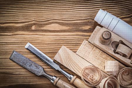 scobs: Engineering drawing planer chisels wooden bricks shavings on wood board.