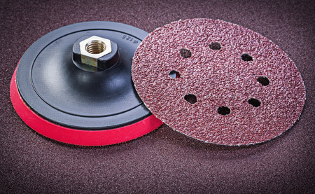 Abrasive discs holder on sandpaper sheet top view. Banco de Imagens
