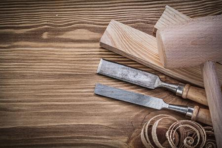 stud: Wooden hammer stud firmer chisels planning chips on vintage wood board.