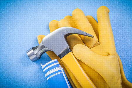 claw hammer: Claw hammer safety gloves rolled construction drawings on blue background. Stock Photo