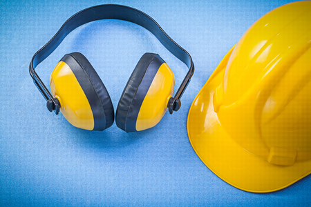 Earmuffs: Earmuffs building helmet on blue background construction concept.