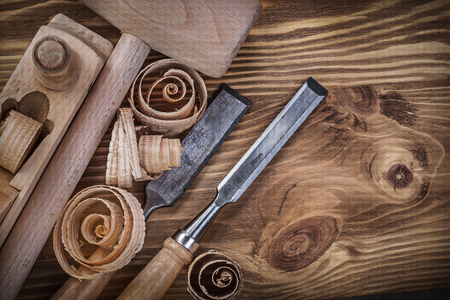 scobs: Wooden mallet shaving plane flat chisels curled shavings on vintage wood board construction concept.