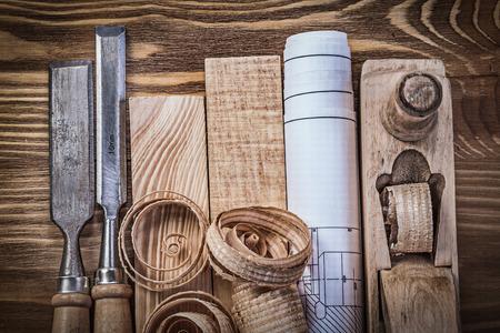 scobs: Engineering drawing shaving plane chisels wooden bricks shavings on wood board.