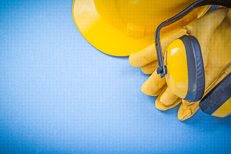 ear muffs: Ear muffs protective gloves hard hat on blue background construction concept.