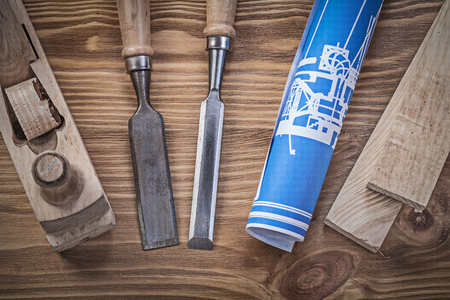 wood planer: Blue rolled up construction drawing planer chisels wooden studs on wood board.