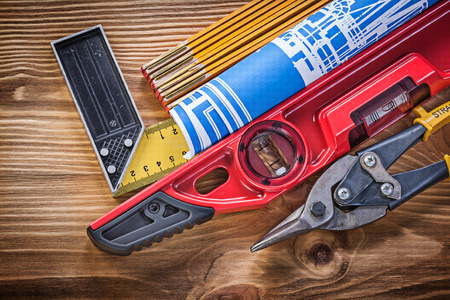 square ruler: Construction level tin snips engineering drawing wooden meter square ruler on wood board. Stock Photo