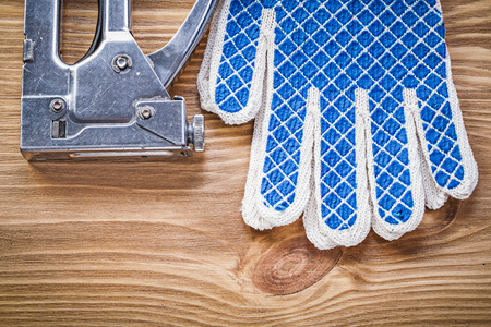 staple gun: Collection of construction stapler safety gloves on wooden board.