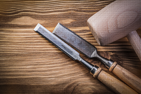 chisels: Wooden hammer chisels on vintage wood board construction concept.