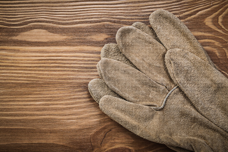 protective gloves: Brown protective gloves on vintage wood board construction concept.