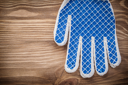 working gloves: Pair of safety working gloves on wood board maintenance concept.