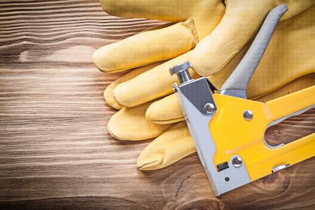 staple: Staple gun safety gloves on wooden board construction concept. Stock Photo