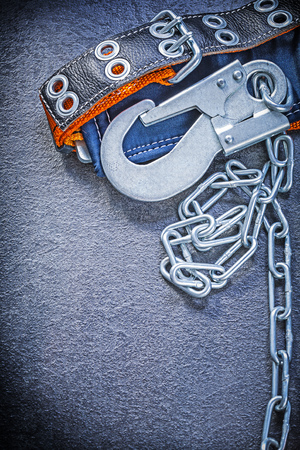 cinturon seguridad: cintur�n de seguridad del edificio con la cadena de metal sobre fondo negro concepto de la construcci�n.