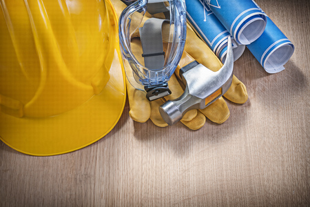 protective work wear: Protective work wear claw hammer rolled construction plans on wooden board.