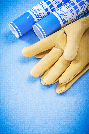 safety gloves: Heap of construction plans leather safety gloves on blue background. Stock Photo
