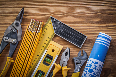 building maintenance: Composition of building tools on vintage wooden board top view.