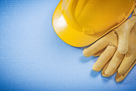 yellow hard hat: Yellow hard hat safety gloves on blue background construction concept. Stock Photo