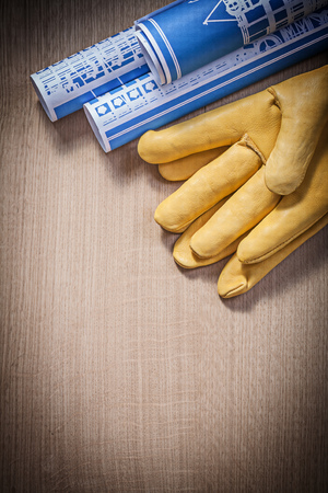 protective gloves: Blue blueprints leather protective gloves on wooden board construction concept.