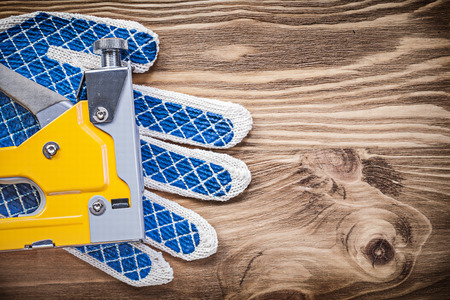 working gloves: Staple gun working gloves on wooden board copy space construction concept. Stock Photo
