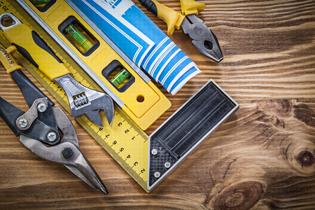 construction level: Construction level blueprint try square pliers steel cutter adjustable wrench on wooden board.