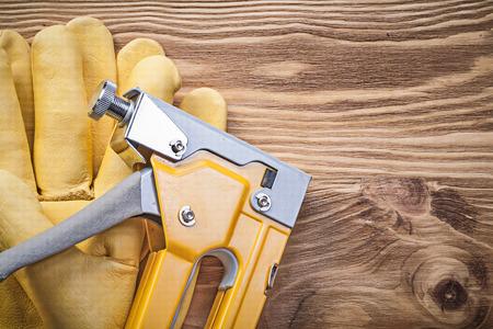staple gun: Staple gun protective gloves on wooden board construction concept.