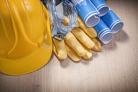 protective gloves: Safety helmet protective gloves glasses blueprints on wooden board construction concept.