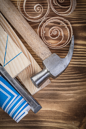 scobs: Blue construction plan claw hammer firmer chisel wooden studs shavings on wood board.