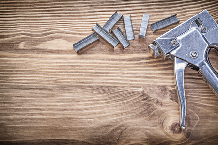staple gun: Stapler gun heap of staples on wooden board construction concept. Stock Photo
