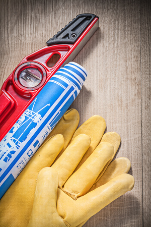 drawing up: Composition of safety gloves construction level blue rolled engineering drawings on wooden board. Stock Photo