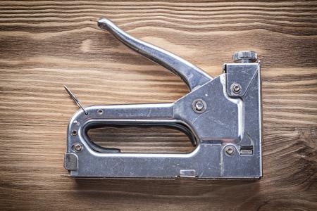 staple gun: Metal staple gun on wooden board construction concept. Stock Photo