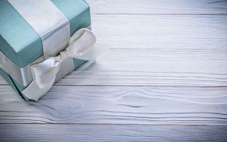 giftbox: Blue giftbox with white ribbon on wood board copy space celebrations concept.