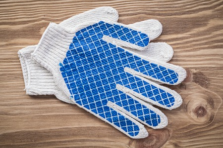 protective gloves: Protective gloves on wooden board construction concept. Stock Photo