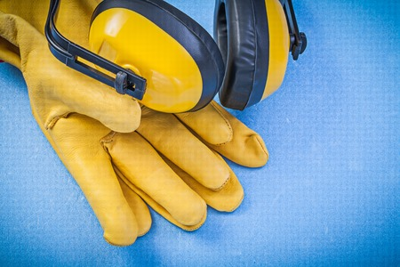 ear muffs: Noise reduction ear muffs leather protective gloves on blue background construction concept.