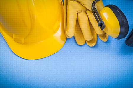 Earmuffs: Noise insulation earmuffs protective gloves building helmet on blue background construction concept.