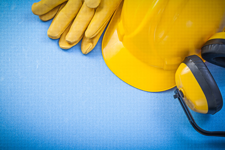 Earmuffs: Noise reduction earmuffs safety gloves building helmet on blue background construction concept.